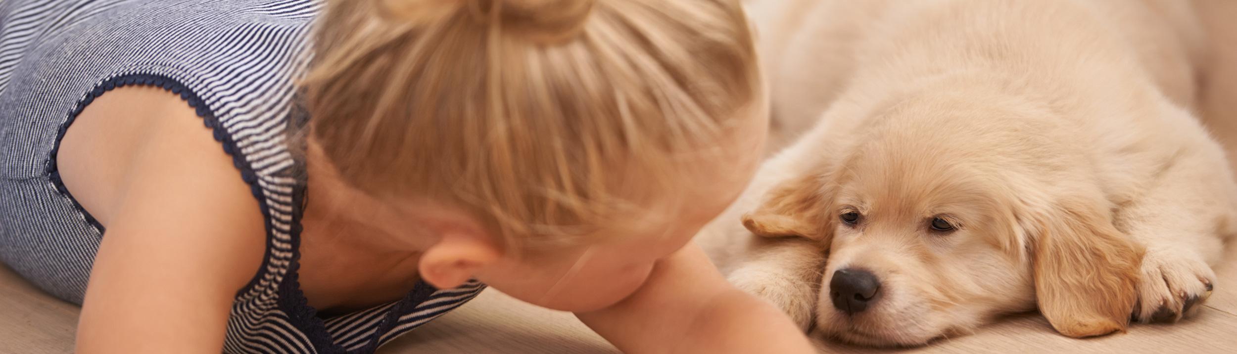 Mädchen mit Hund liegen auf dem Boden und geniessen den Warmen Fussboden dank der Fussbodenheizung der Urs Metzger AG.