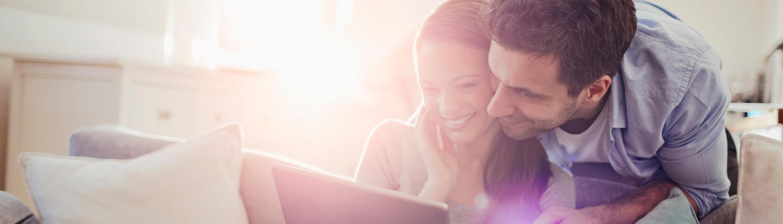 Frau und Mann schauen auf ein Tablett. Die Heizungssanierungen der Firma Urs Metzger ganz einfach online anfragen.