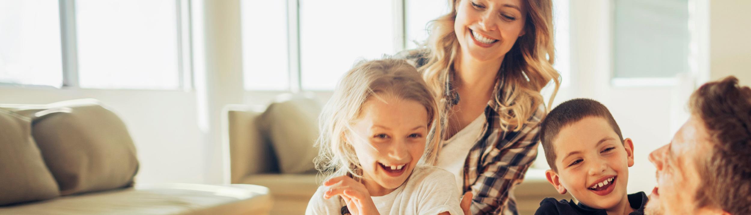 Familie mit Kindern am spielen und lachen im Wohnzimmer.Kuschelig warme Winter dank Heizungen der Urs Metzger AG. Fühlen Sie sich Zuhause wohl dank Heizungen der Urs Metzger AG.
