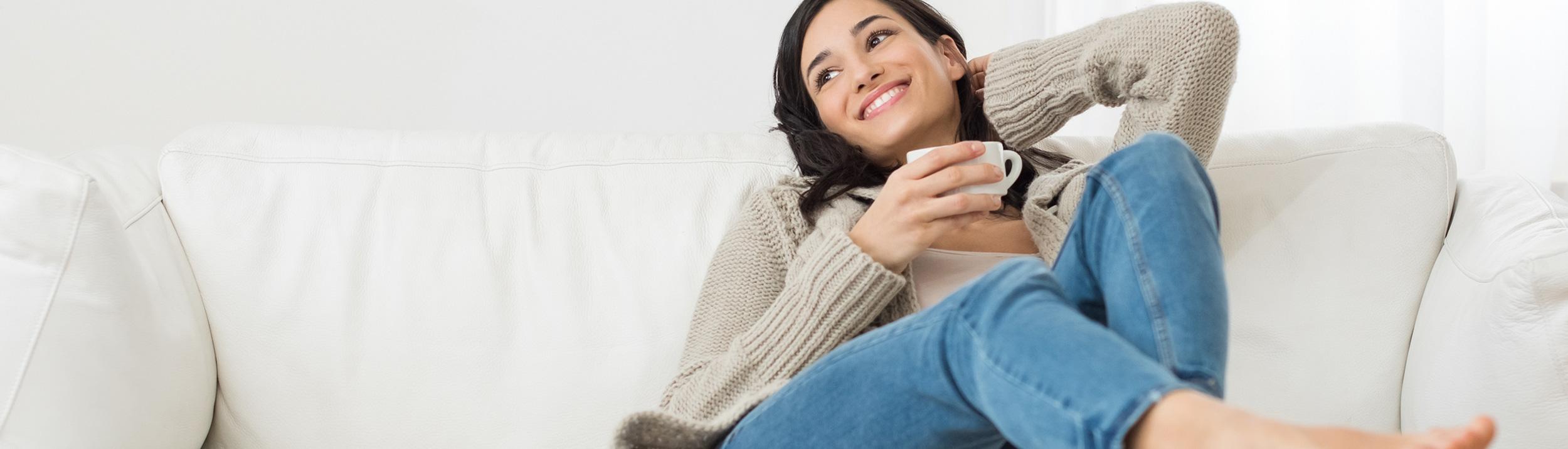 Frau sitzt auf einem Sofa und trinkt einen Tee. Die Komfortlüftungen von der Firma Urs Metzger AG machen das Leben für Allergiker leichter.