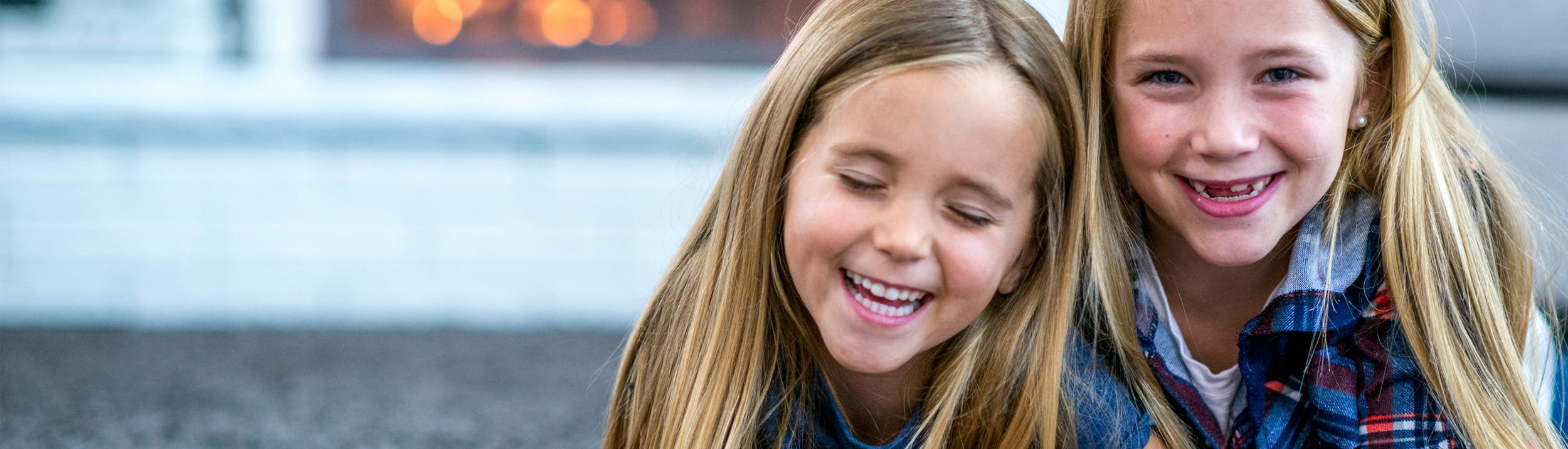 Zwei Mädchen spielen am Boden und lächeln. Dank der Firma Urs Metzger AG geniessen Sie ein schön warmes Zuhause.