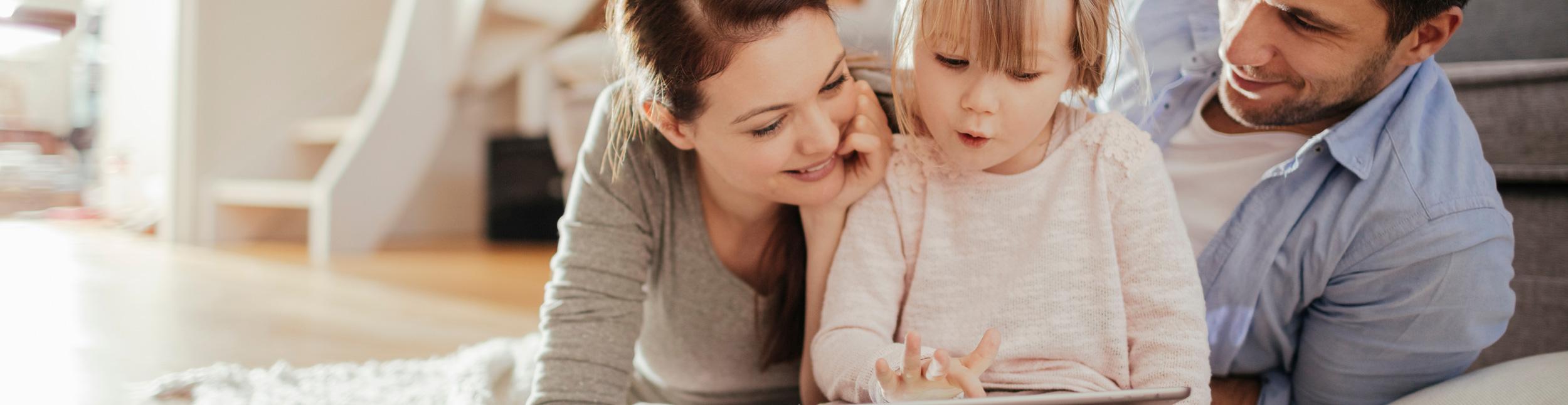Familie mit Kind sitzen am Boden im Wohnzimmer und schauen auf ein Tablett. Kuschelig warme Winter dank Heizungen der Urs Metzger AG. Fühlen Sie sich Zuhause wohl dank Heizungen der Urs Metzger AG.