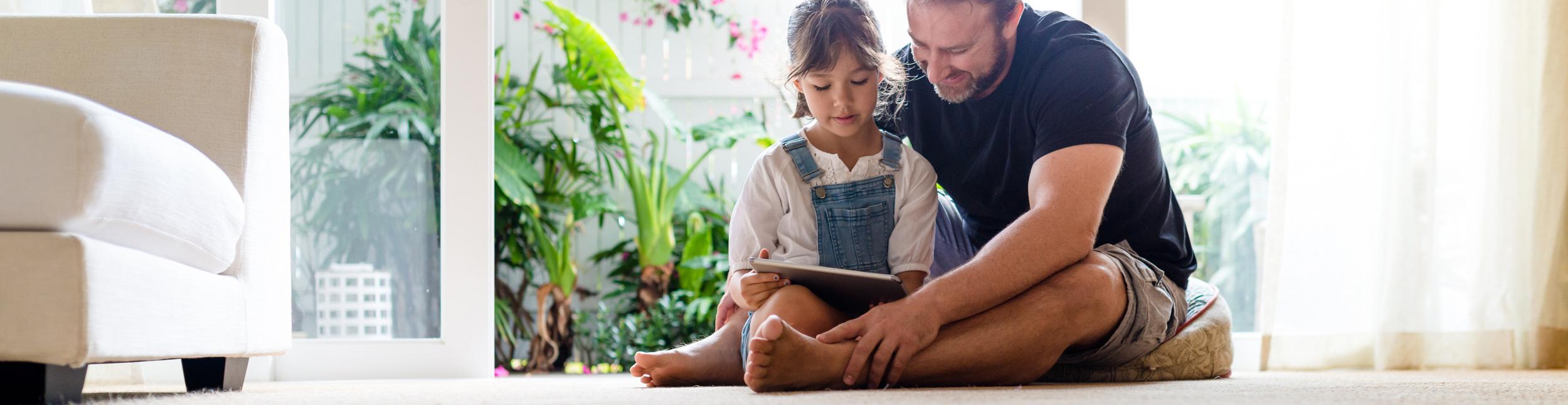 Vater mit Kind sitzt am Boden im Wohnzimmer und schaut auf ein Tablett. Fühlen Sie sich Zuhause wohl dank Heizungen der Urs Metzger AG.