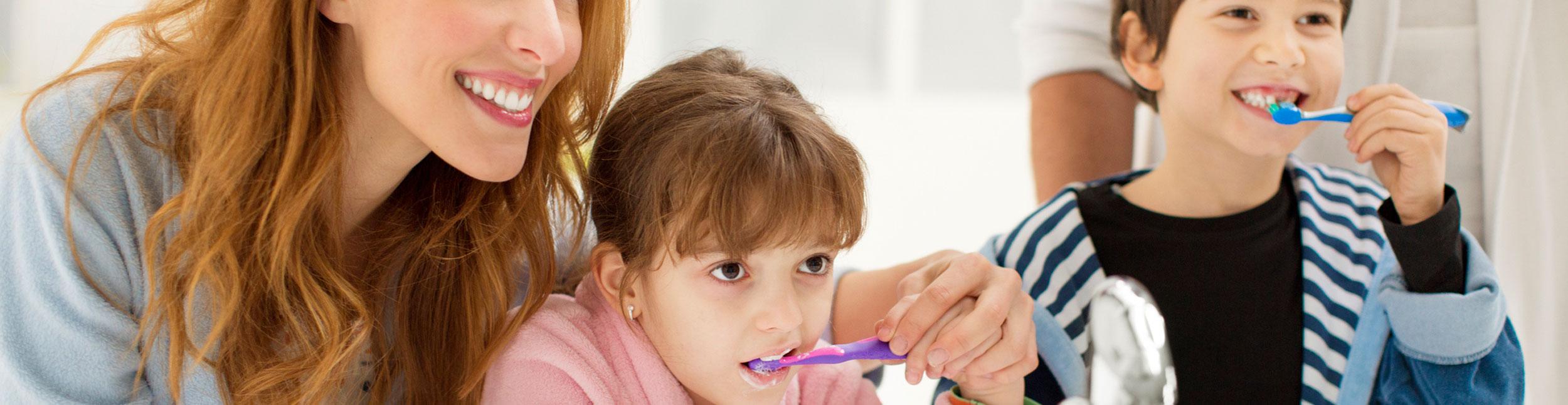 Familie mit Kindern am Zähneputzen und lachen.