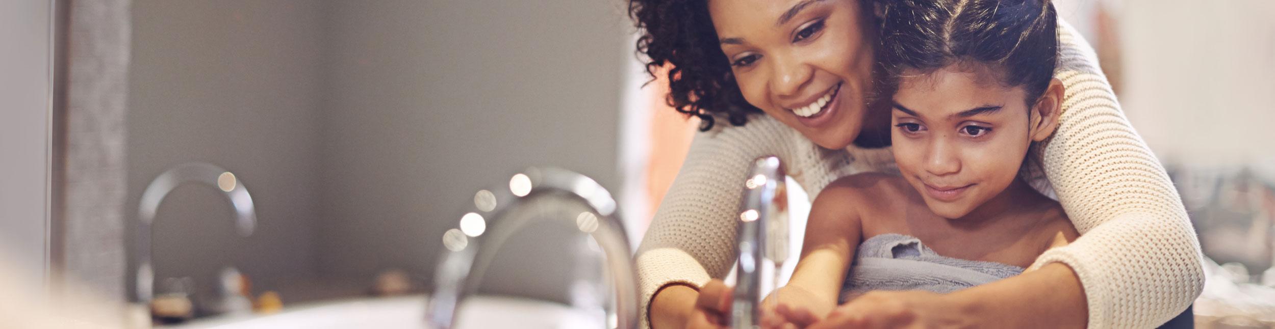 Mutter mit Ihrem Mädchen vor einem Lavabo am Händewaschen. Urs Metzger AG ist Ihr Partner in Sachen Sanitär.