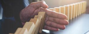 Dominosteine aus Holz mit einer Hand die sie stoppen.