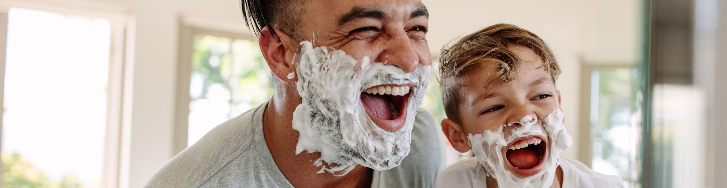 Mann und Junge lachen mit Rasierschaum im Gesicht.