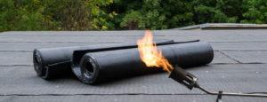 Zwei Bitumenrollen mit einem Brenner auf einem Flachdach. Die Firma Urs Metzger ist Ihr Partner rund ums Thema Flachdach.